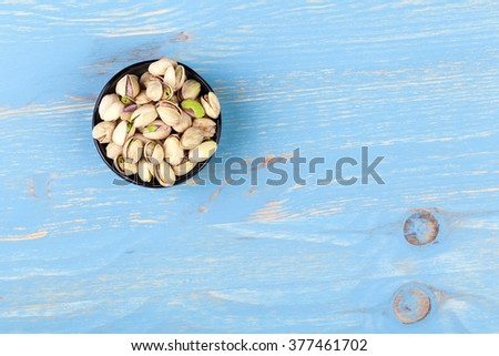 Black bowl of pistachios on turquoise wooden background - stock photo