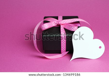 Black box present gift with pink polka dot ribbon and white heart shape gift tag for Mothers Day, birthday, Easter, Christmas, Valentine or special occasion gift, with copy space for your text here. - stock photo
