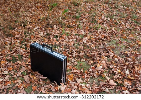 Black briefcase left in the field - stock photo