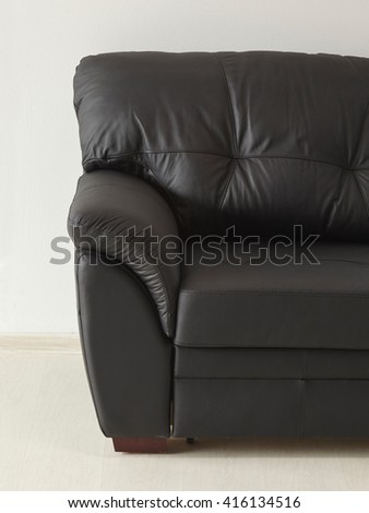 Black brown leather sofa isolated against the wall