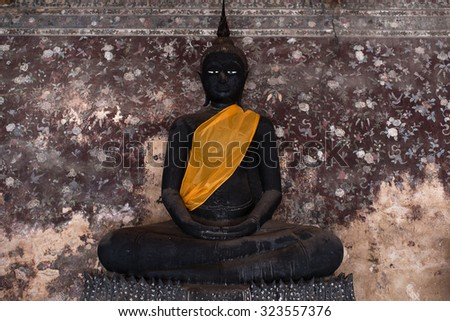 Black Buddha Image with Ancient Floral Pattern Wallpaper Background (Soft Focus on Buddha Face) - stock photo