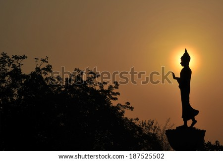Black buddha silhouette with golden sky - stock photo