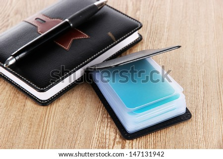 Black business card holder notebook and pen on wooden background - stock photo