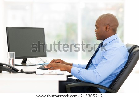black business man at desk typing on keyboard
