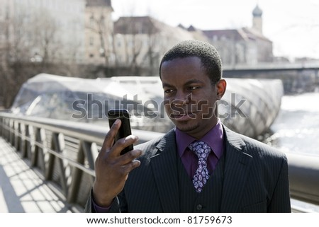 Black business man with black smart phone and modern and old architecture in background. Grey suit with violet chemise - stock photo