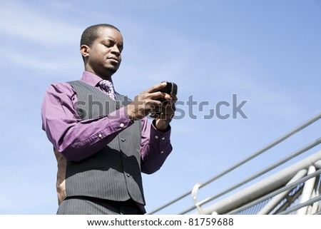 Black business man with modern smart phone, outdoor with blue sky - stock photo