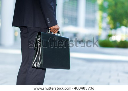 Black businessman carrying a briefcase - stock photo