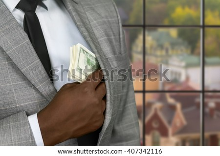 Black businessman hiding cash. Wealthy man on urban background. Criminal is always cautious. Getting away from law. - stock photo