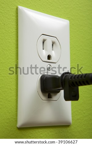 black cable plugged in a white electric outlet mounted on green wall - stock photo