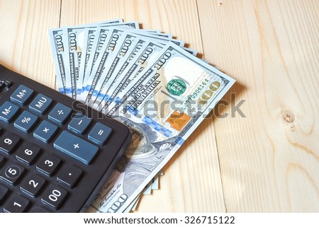 Black calculator and dollars on a wooden background with place for text - stock photo