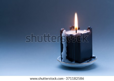 Black candle with a flame and drips. Dark blue gradient background. Greeting holiday card template. copy space - stock photo