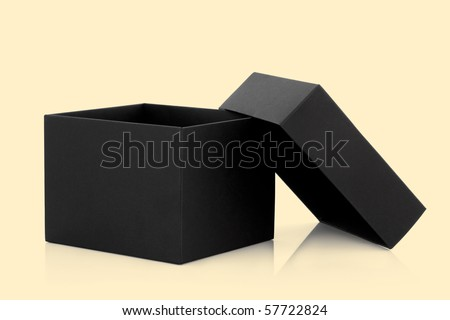 Black cardboard box with the lid off over pastel yellow background with reflection. - stock photo
