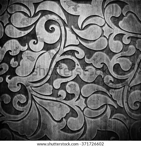 Black carved ornament on wooden texture - stock photo