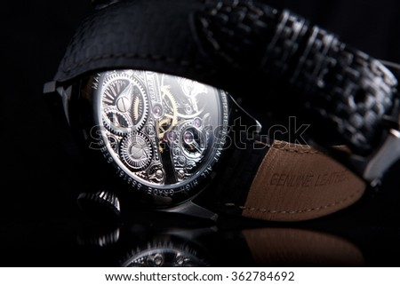 Black case skeleton watches with blue hands and blue sapphires on black carbon leather strap back side view - stock photo