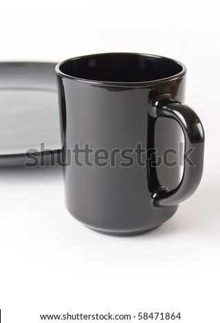 black ceramic cup of coffee and tea in the background part of the black plate