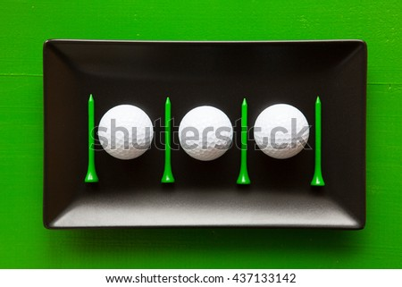 Black ceramic dishes with golf balls and wooden tees on over green background, rectangle dish - stock photo