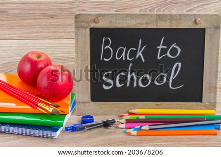 black chalk board with back to school letters and school supplies on table - stock photo