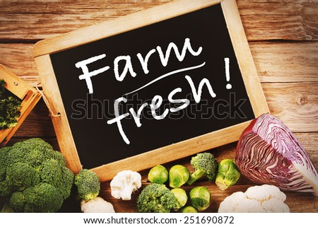 Black Chalk Board with Farm Fresh Texts with Assorted Organic Veggies on Sides on Top of Wooden Table. - stock photo