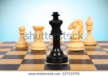 Black Chess King and white chess pieces - stock photo