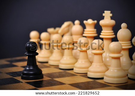 Black chess pawn standing in front of white chess pieces - stock photo