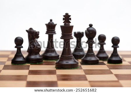 Black chess pieces in formation (focus on black king) - stock photo