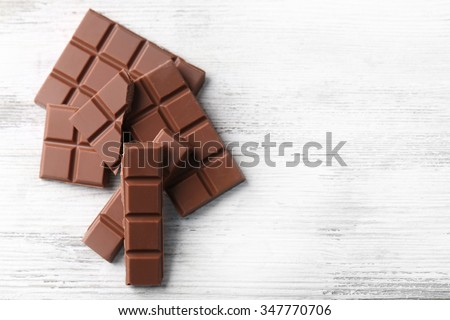 Black chocolate pieces on color wooden background - stock photo
