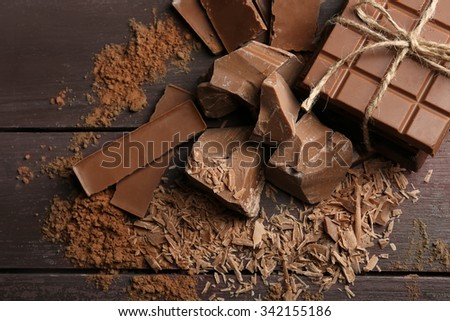 Black chocolate pieces with spices on wooden background - stock photo