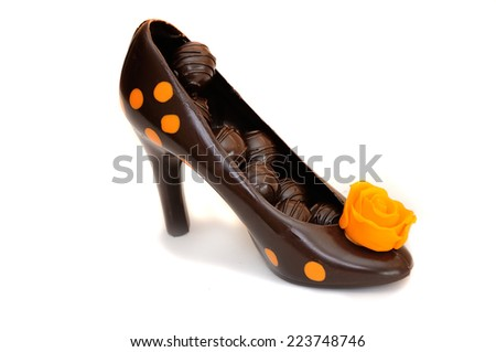 black chocolate shoe with candy and orange rose - stock photo