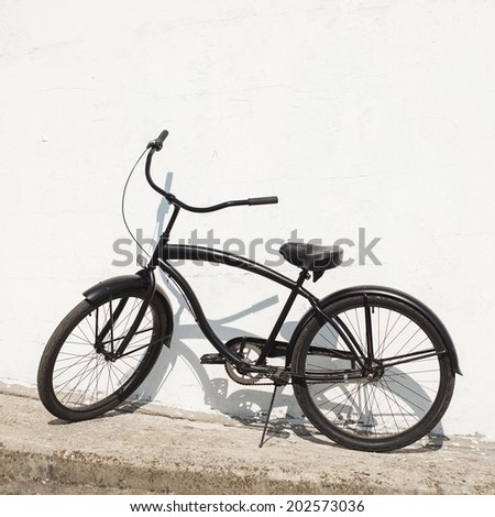 Black city bicycle cruiser standing by next white wall. Outdoor - stock photo