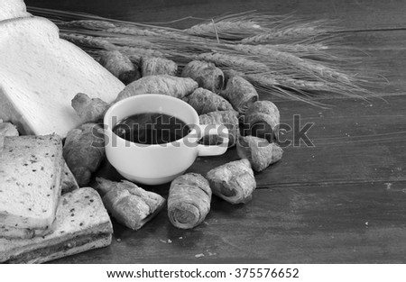 Black Coffee and many kind bread on old wooden plate / Black and white style - stock photo