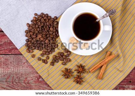 Black coffee, cinnamon and cane sugar on a table - stock photo