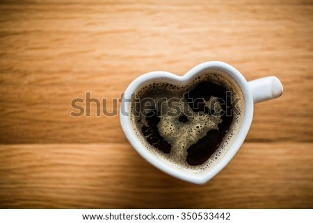 Black coffee, espresso in heart shaped cup. Love concept, Valentine's Day. View from the top, vintage - stock photo