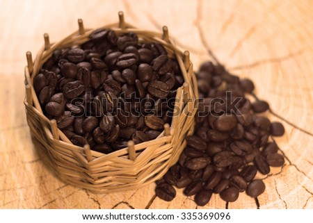 Black coffee grains  in a vintage wicker basket on a vintage wooden background