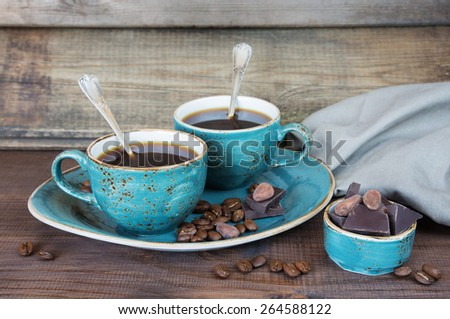 Black coffee in blue vintage cups, cookies and chocolate on a old dark wooden boards - stock photo