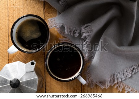 Black coffee in enamel mug and coffeemaker on a wooden table (top view) - stock photo