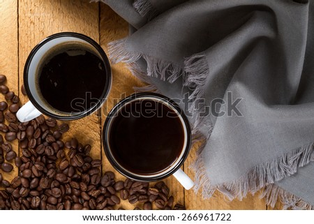 Black coffee in enamel mug on a wooden table (top view) - stock photo
