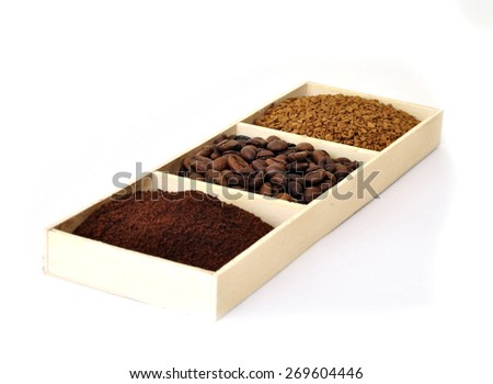 Black coffee in four different forms: beans, ground, granulated and sublimated in a wooden tray - stock photo