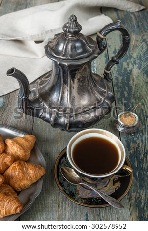 Black coffee in vintage cup, croissants on an old tin plate and antique silver coffee pot on a old dark wooden boards - stock photo