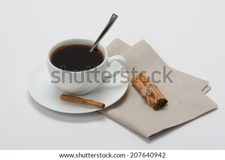 Black Coffee In White Cup And Cinnamon Sticks On Folded Natural Linen Napkin. White Background. - stock photo