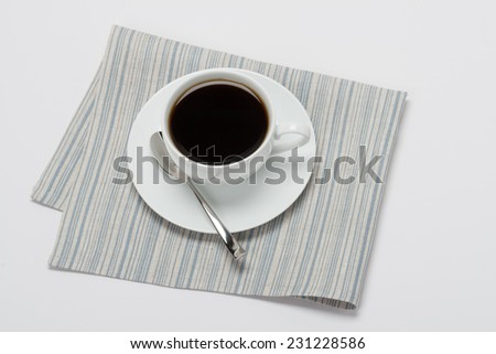 Black Coffee In White Cup On Folded Natural Linen Napkin. White Background. - stock photo
