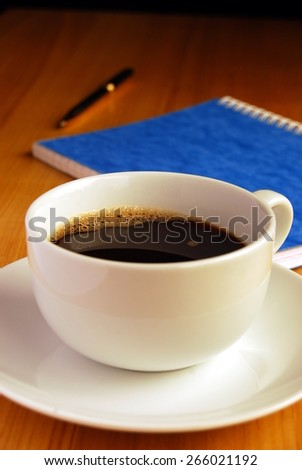Black Coffee on a Desk With Notebook and Pen in the Background - stock photo