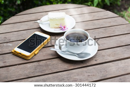 Black coffee phone and cakes on a wooden table in the garden, soft focus - stock photo