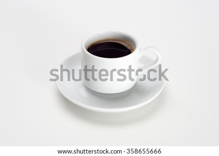 Black coffee with bubbles in white cup with saucer.