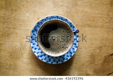 Black coffee with crema in an elegant cup and saucer with a blue pattern on a wooden table.