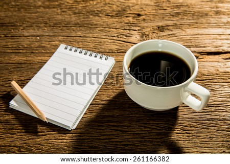 black coffee with note paper and pencil on wood table. - stock photo