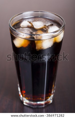 Black cola in a glass with ice real, not plastic