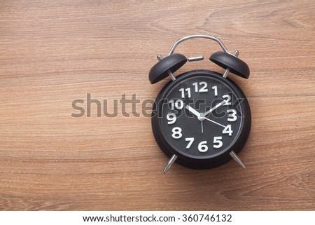 Black color bell alarm clock on wood background - stock photo