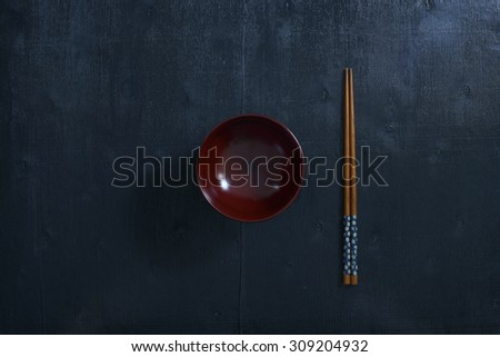 Black color wooden table top view. On the table are the Japanese wooden  chopsticks, bowl. - stock photo