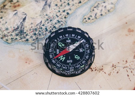 Black compass on map - stock photo