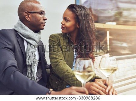 Black couple having a conversation at a cafe outdoors in the spring - stock photo